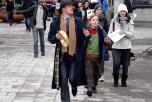 En clown som slåt på en tamburin går längst fram i ett demonstrationståg för fred.
