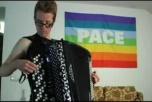 """Oscar Schön spelar dragspel framför en regnbågsflagga med texten """"PACE"""""""