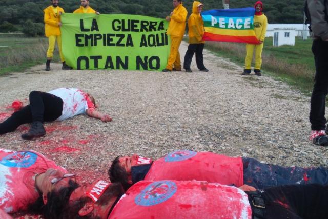 Aktivister spelar döda på en väg. Någon har hällt rosa färg över dem. Bakom dem en banderoll på spanska.