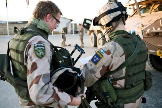 Två soldater pratar med varandra, de ser ut att vara i Afghanistan