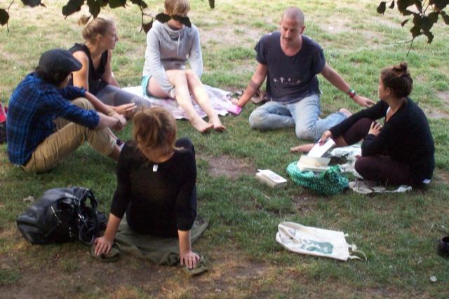 Sex personer sitter i en ring på en gräsmatta och pratar