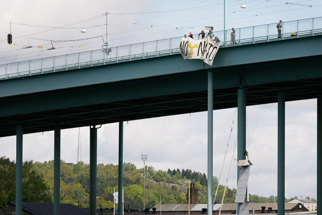 """En banderoll hänger från en bro, med texten """"No Nato"""" och en kärnkraftssymbol"""