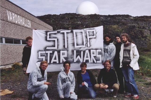 """Sju personer håller upp en banderoll med texten """"Stop Staw Wars"""" framför Vardö spionbas."""
