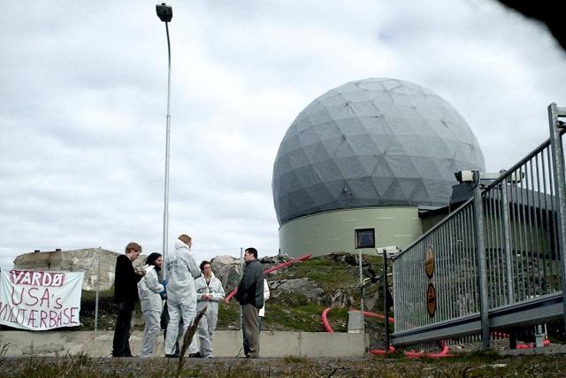 Fem personer står framför en stor grind, och en mycket stor klotformad antenn