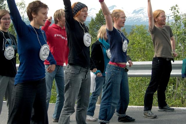 En grupp personer med en knuten högerhand i luften