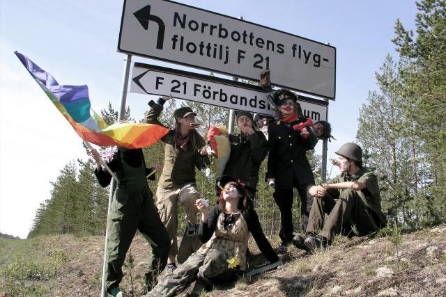 Clownarmé framför vägskylt som pekar mot Norrbottens Flygflottilj F21