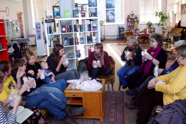 Ett tjugotal personer sitter runt ett bord i en cafélokal