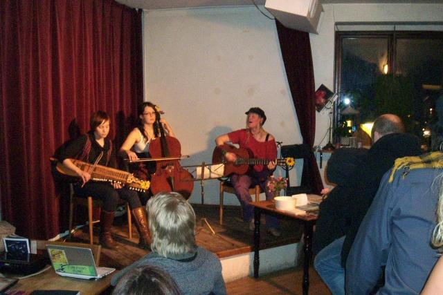 Tre personer spelar musik på en scen, framför publik