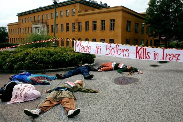 """Fem personer spelar döda på asfalten framför ett stort hus och en banderoll: """"Made in Bofors - kills in Iraq"""""""