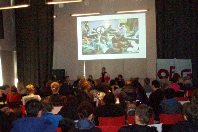 Tre personer håller en föreläsning framför en stor grupp människor. En aktionsbild projiceras på väggen.