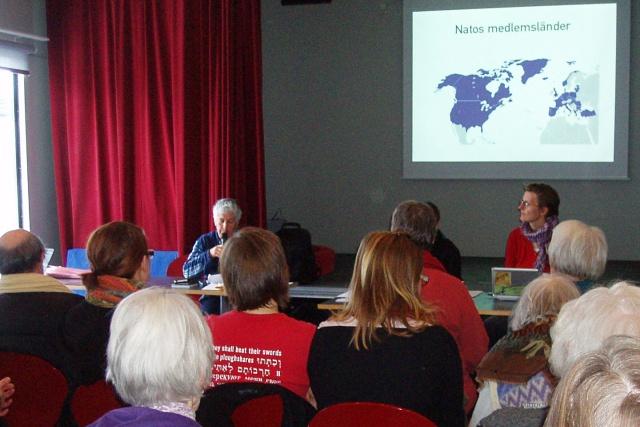 Tre personer håller en föreläsning framför en stor grupp människor. En Natokarta projiceras på väggen.