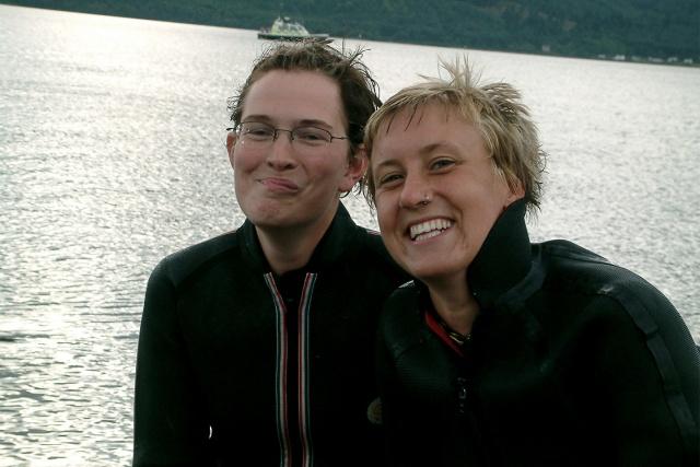 Två personer i våtdräkter på en strand