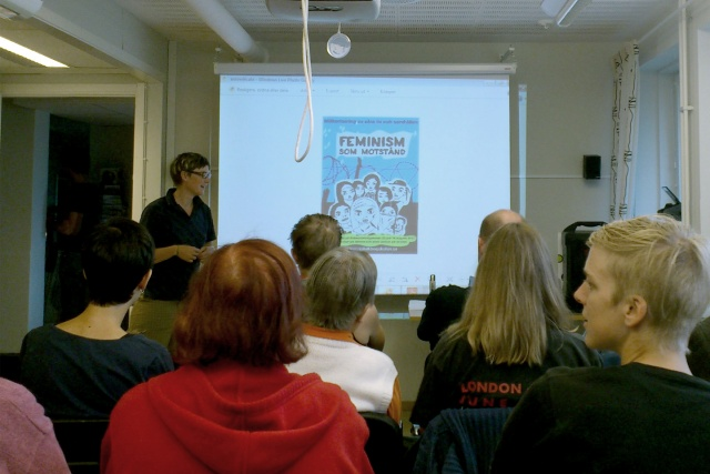 En person föreläser framför en grupp människor