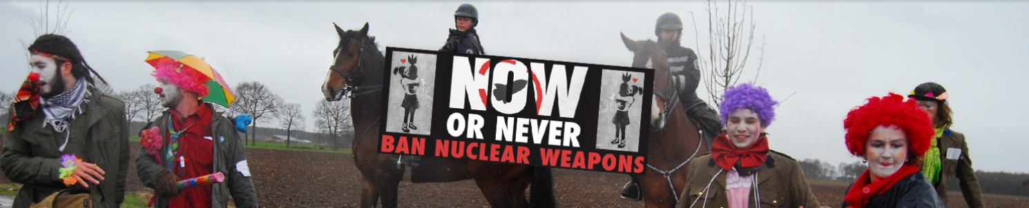 "Fyra clowner och två beridna poliser ute på landet. Text: ""Now or never. Ban nuclear weapons."""