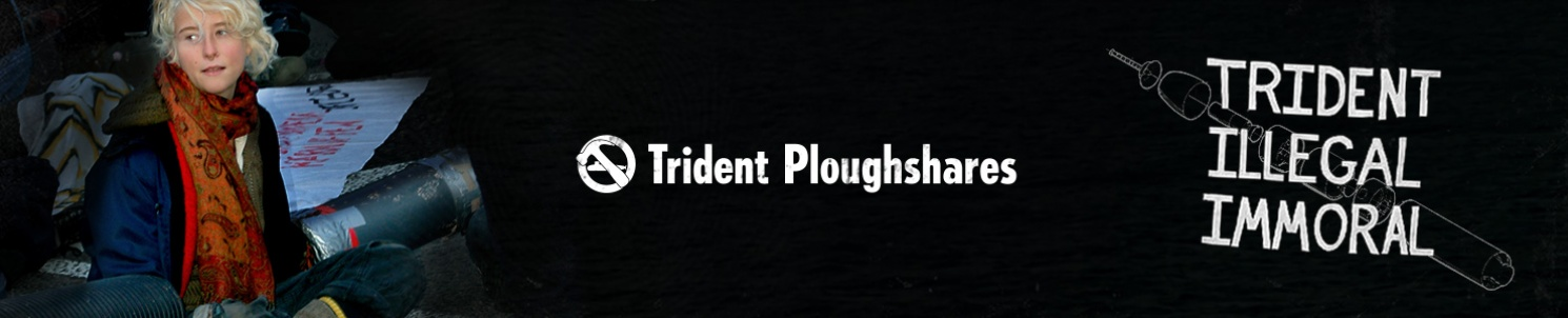 "En ung person blockerar en väg. Text: ""Trident Ploughshares - Trident. Illegal. Immoral.""."